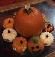 Small real pumpkin surrounded by miniature fake plastic pumpkins and one miniature homemade felted jack-o'-lantern