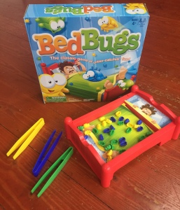 Bed Bugs game by Hasbro set up with tweezers beside and box behind bed