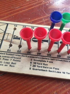 Close up of wooden football peg game with red blue and green pegs in board
