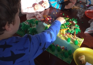 Child adding pieces to jungle forest garden park building brick play set