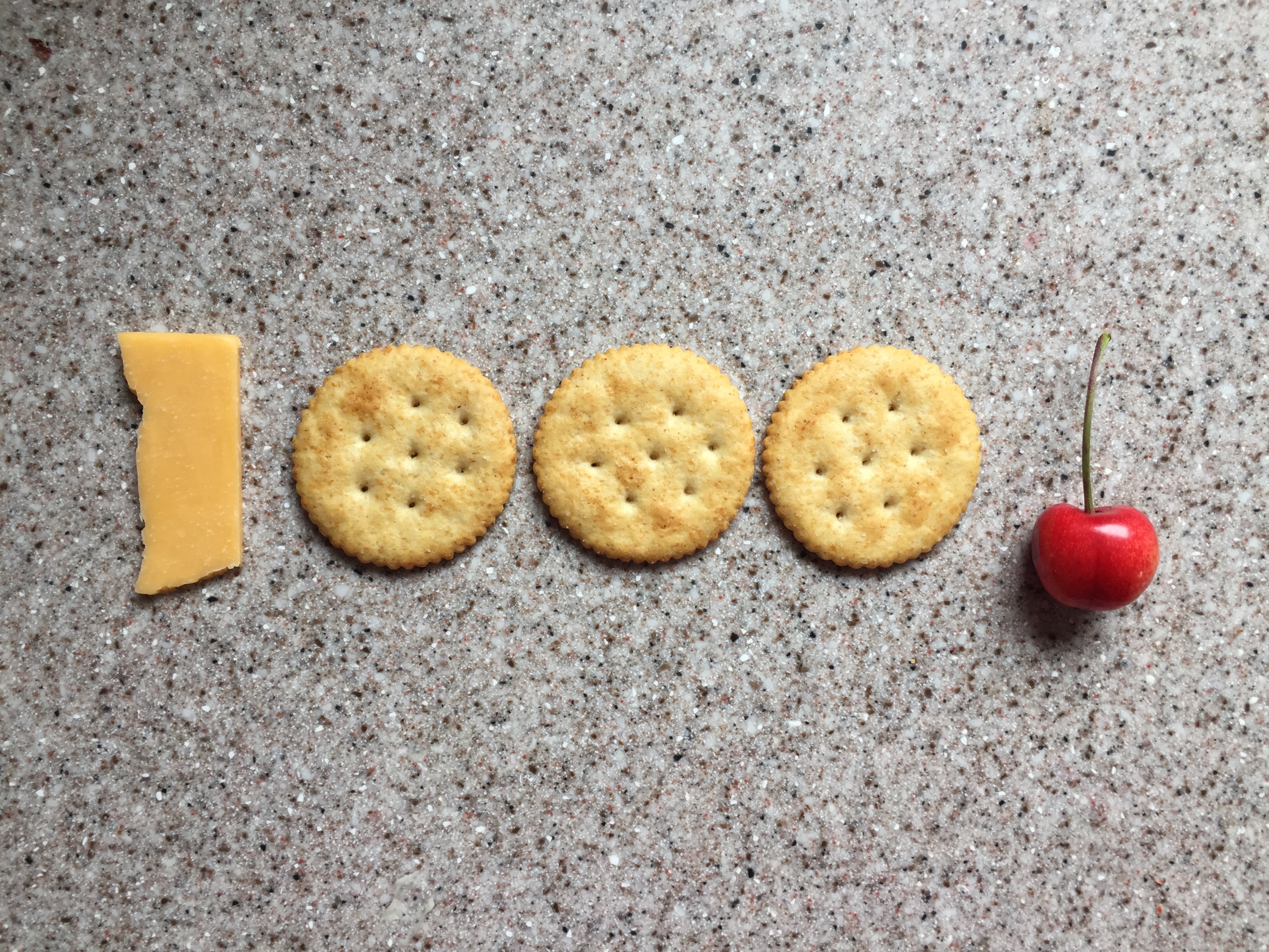 1000 number made from slice of cheese, round Ritz crackers, and a cherry for an exclamation mark