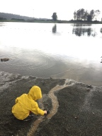 Child in raincoat digging in sand next to