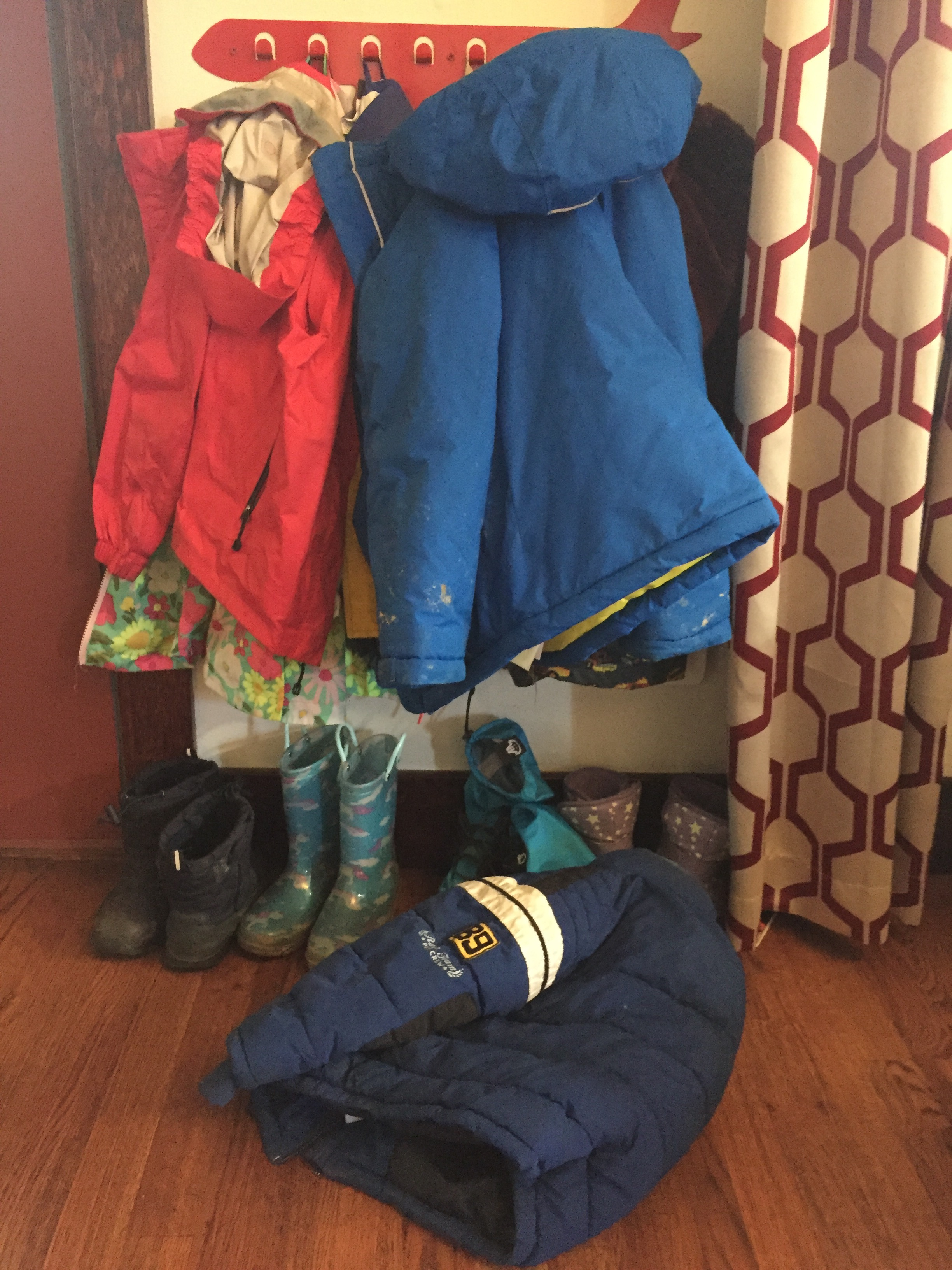 Kids jackets, rain coats, winter coat, rain boots, and snow boots hanging on airplane coat rack and sitting on floor