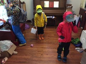Kids getting ready to leave house in rain jackets, rain pants, hats, gloves, boots, and face masks