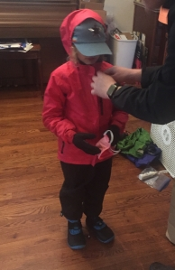 Child getting ready to leave house wearing pink rain jacket, black rain pants, waterproof boots, hat, gloves, and face mask