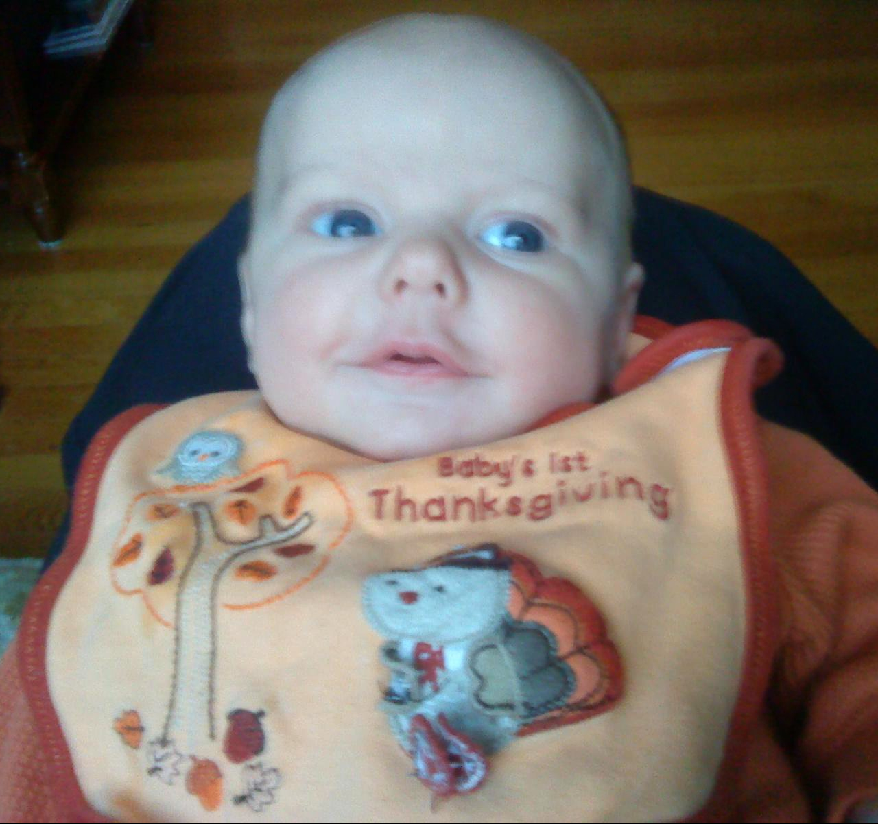 Six week old infant wearing baby's first thanksgiving bib with turkey