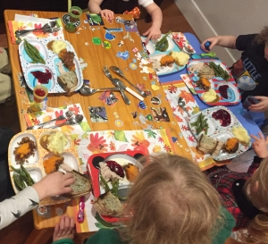 Kids table at Thanksgiving dinner with food and leaves decorating table