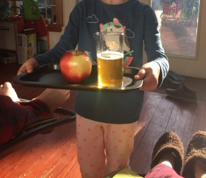 Child carrying tray with apple and drink while parents lounge inside