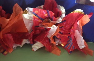 Three tissue paper flowers in a row made from striped white paper, striped red paper, and orange paper by eight year old