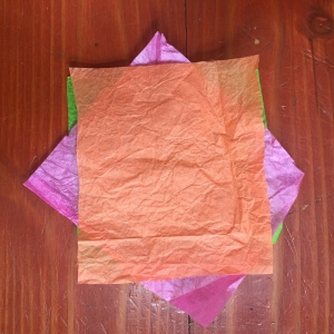 Tissue paper in pink, green, and orange stacked 90 degrees offset on each layer
