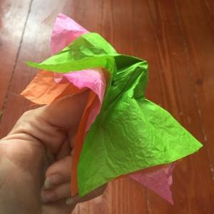 Tissue paper flower making twisting paper around finger