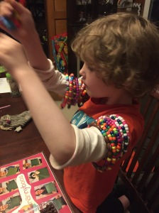 Child making bracelets from pony beads and pipe cleaners chenille stems and wearing them in stacks on arms