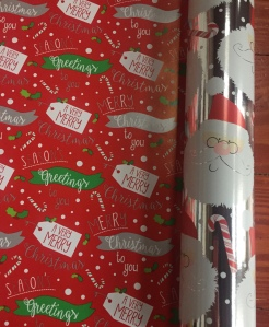 Reversible jumbo roll wrapping paper Santa heads on silver background and Very Merry gift tags on red background