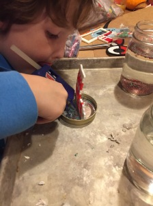 Child using hot glue gun to attach metly bead ornament to inside of jar lid on a cookie sheet
