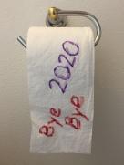 Bye Bye 2020 written on toilet paper handing on holder on wall