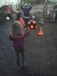 Kids playing with glowcity light up soccer ball in black and orange on brick patio at dusk
