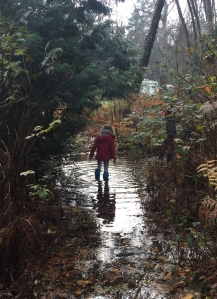 Girl wearing Mymayu Traveler rain boots for kids in giant puddle in the woods