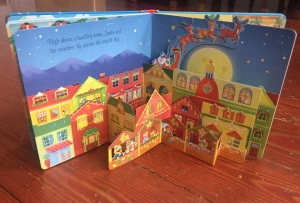 Pop-Up Christmas board book open to city page with Santa and sleigh coming out behind buildings