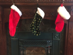 Three stockings in red and green hung over fireplace