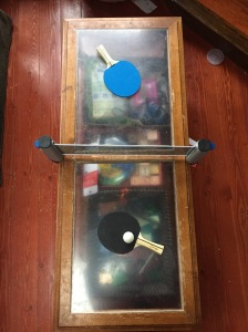Champion Sports Anywhere Table Tennis set up on coffee table as seen from above with paddles in blue and black and ping pong ball
