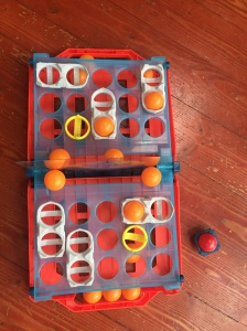 Battleship shots game set up with orange balls and red ball on side