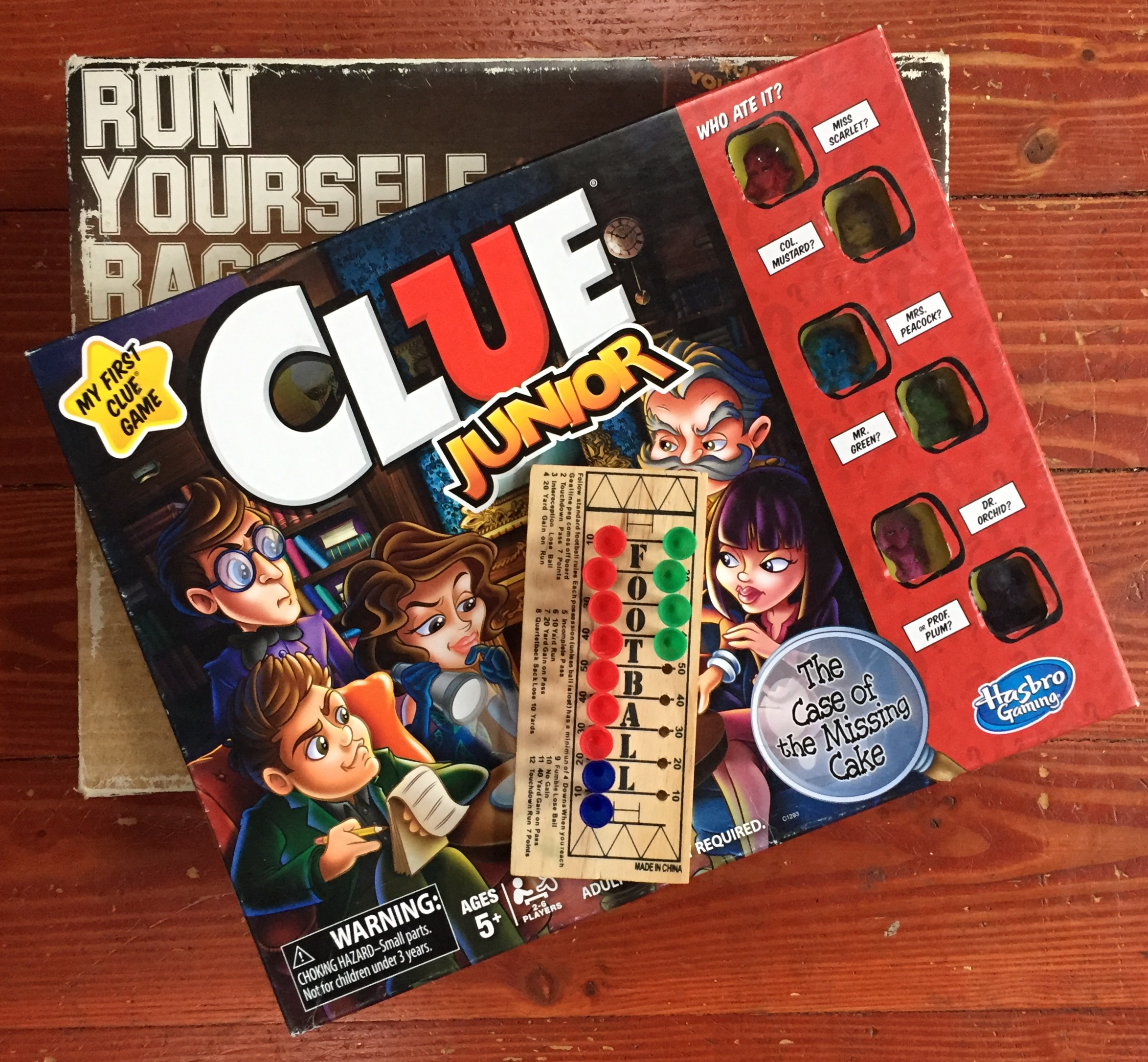 Run Yourself Ragged obstacle marble game, Clue Junior, and Football peg game in stack on hardwood floor