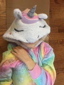 Child wearing blanket sleeper fuzzy fleece onesie pajamas from Saint Eve in pastel rainbow unicorn pattern with sparkles