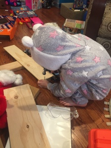 Child wearing blanket sleeper fuzzy fleece pajamas onesie while working with tools hammer nail