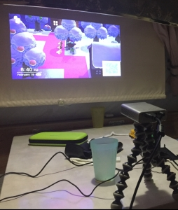 Asus Zenbeam E1 pocket projector projecting Animal Crossing Nintendo Switch game onto closed blinds