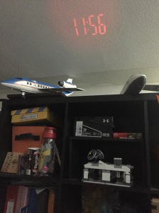 Capella projection alarm clock time displayed on white ceiling over cubby shelves
