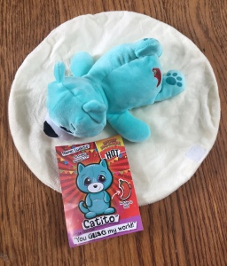Luckito Catito Cutetitoes surprise stuffed animal laying on tortilla blanket with info card