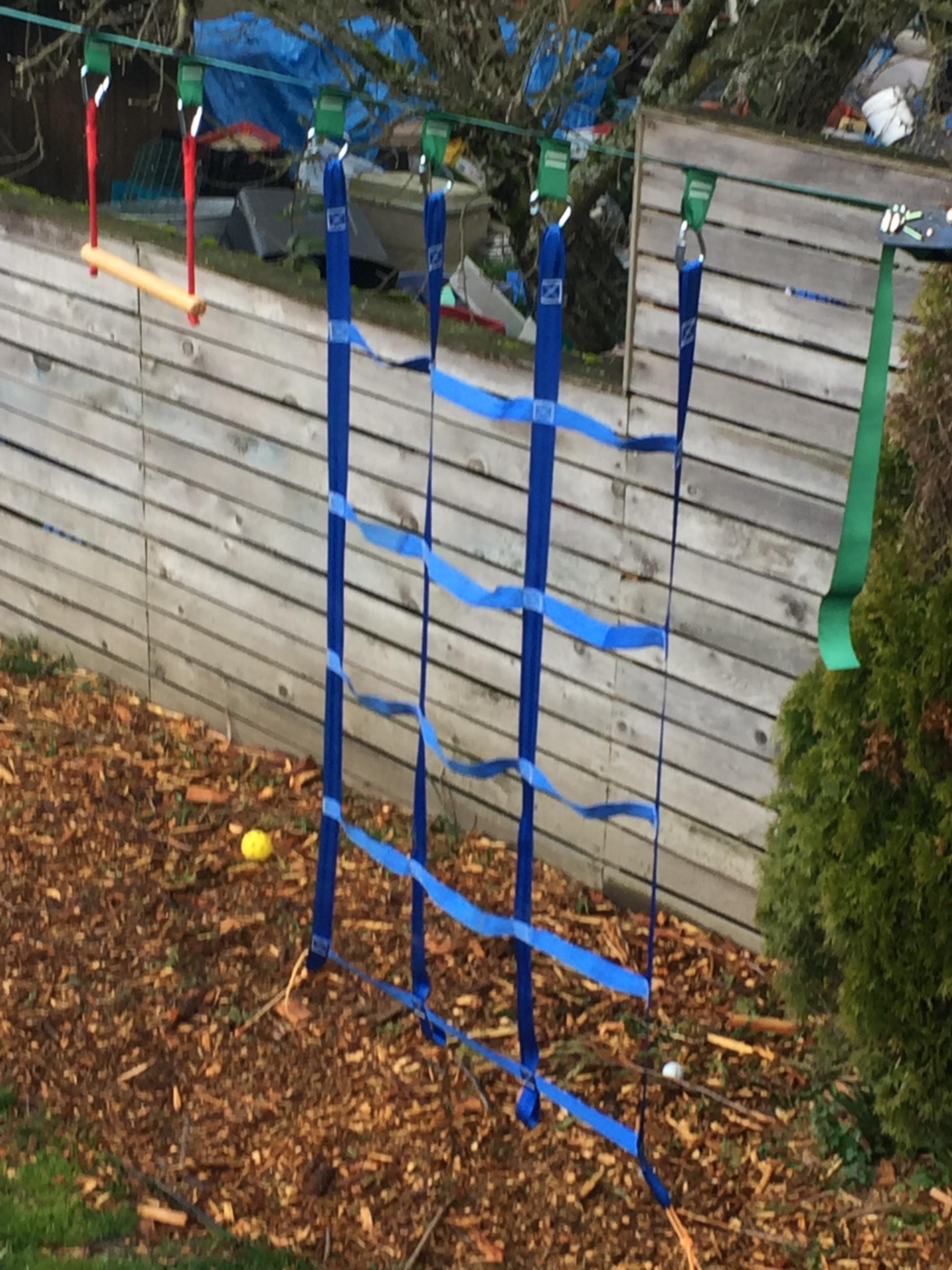 Branton Ninja Warrior Obstacle Course for kids set up along fence in backyard climbing net