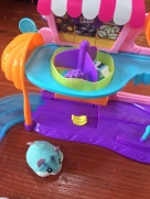 Zuru Hamster in a House tiny toy on wooden floor next to supermarket play set