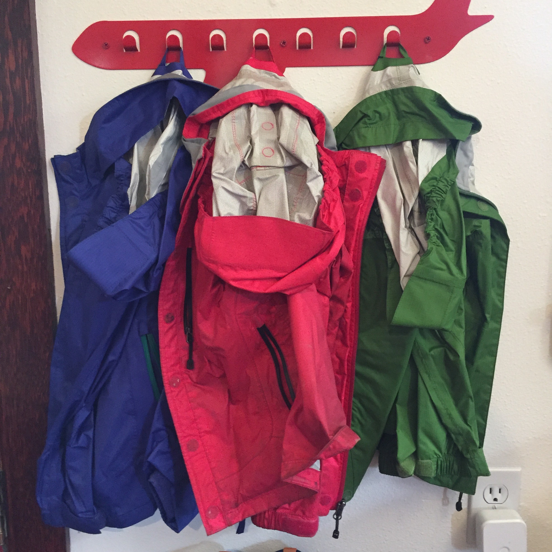 REI Rainwall Kids rain jacket in blue pink and green hanging on airplane coat hook