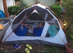 Three kids in sleeping bags inside tent set up in yard