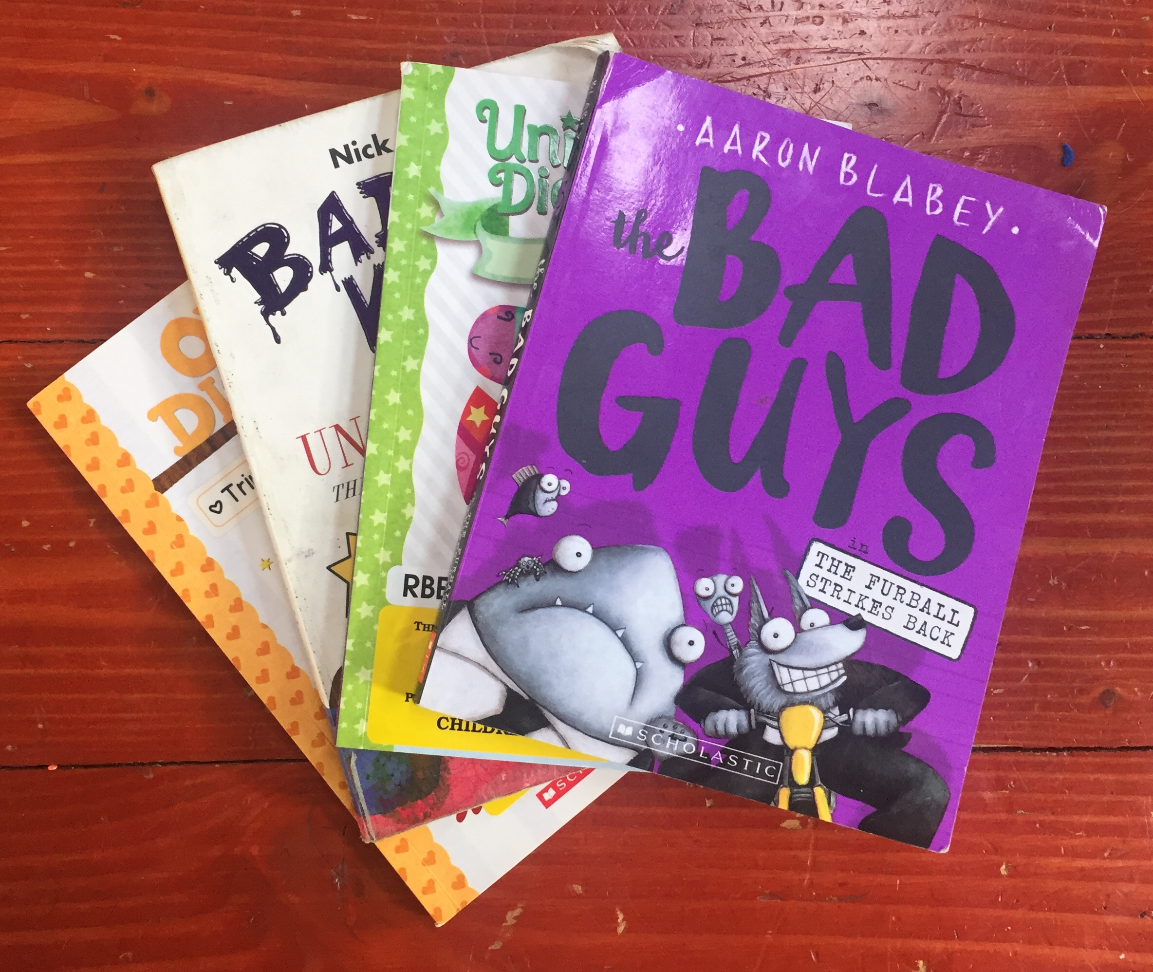 Graphic novels for young readers Bad Guys Unicorn Diaries Bad Kitty Owl Diaries in a stack