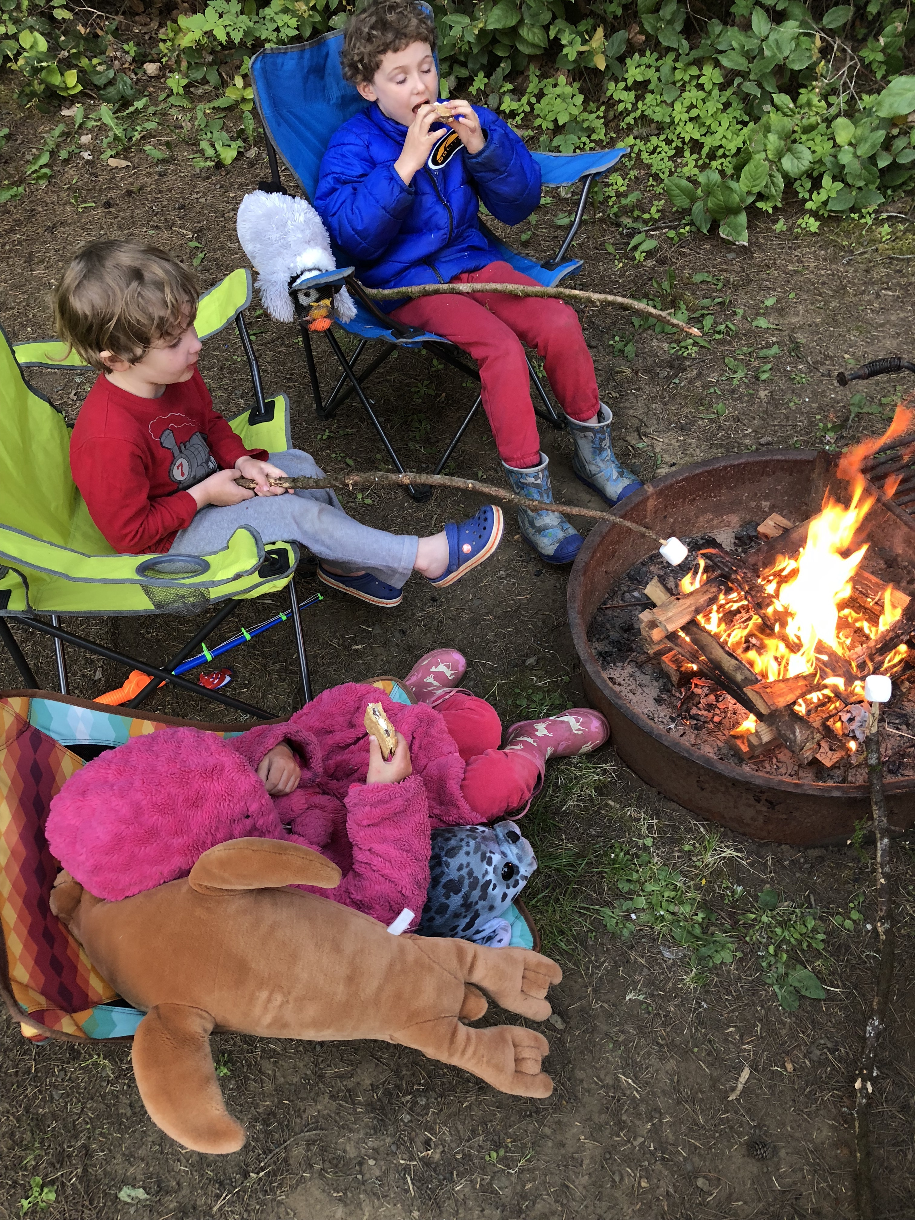 Memorial Day camping kids roasting marshmallows around campfire while sitting in camp chairs