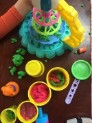 Child's arm with Play Doh containers and toys