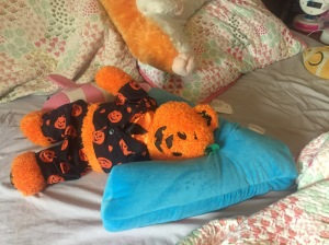 iscream Lettermania V shaped pillow on child's bed with Build a Bear orange bear in pumpkin pajamas laying on it