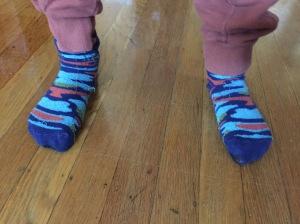 Child's feet wearing TeeHee Naartjie camouflage pattern socks in blue and orange