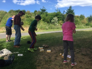 People wide age range kids and adults playing Kingdoms Lawn Game in shade on sunny day
