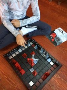 Child playing Khet Laser Chess on hardwood floor