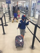 Five year old child puling Mackenzie hard-sided luggage spinner suitcase through airport security