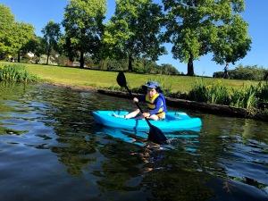 Six year old padding on lake shore in Lifetime Wave Youth Kayak