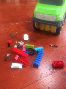 Matchbox Sweep and Keep truck front bristles with LEGO scattered on wooden floor