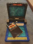 Electronic Battleship game and instruction manual set up on carpeted floor