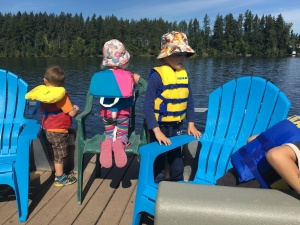 Kids wearing life jackets on dock with bright blue Adirondack chairs