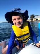 Child on boat raft float on lake wearing bright yellow Ikea life jacket and blue sun hat