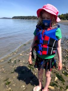 Child wearing life jacket on beach