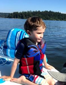 Child wearing life jacket on board boat float raft on lake
